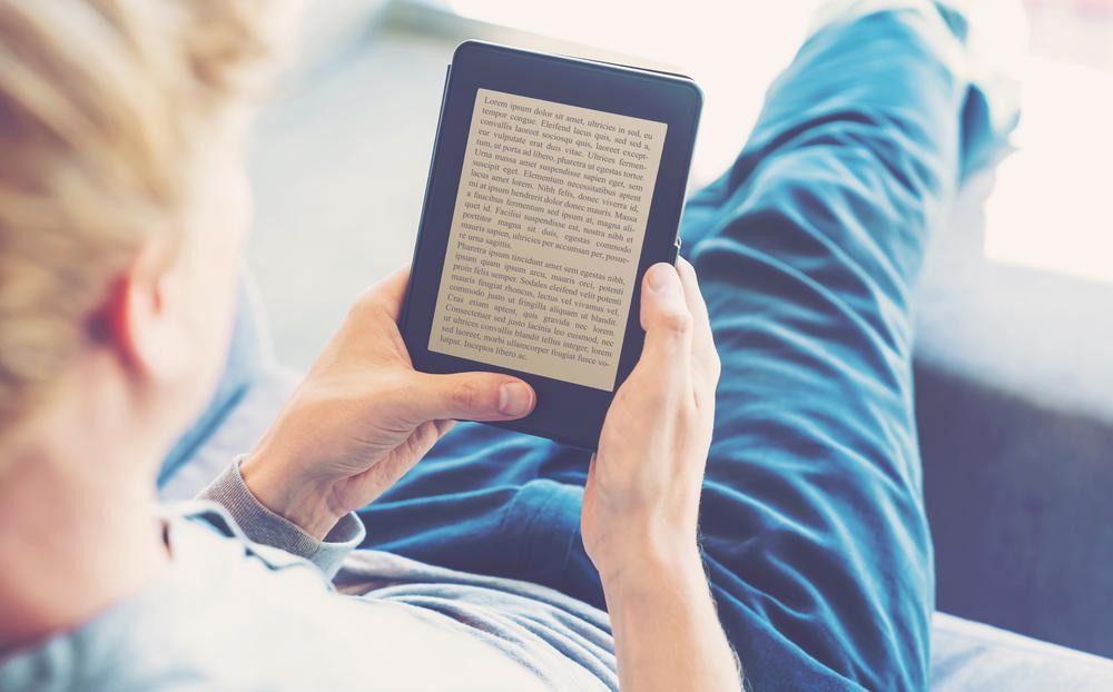 Garçon en train de lire sur sa liseuse